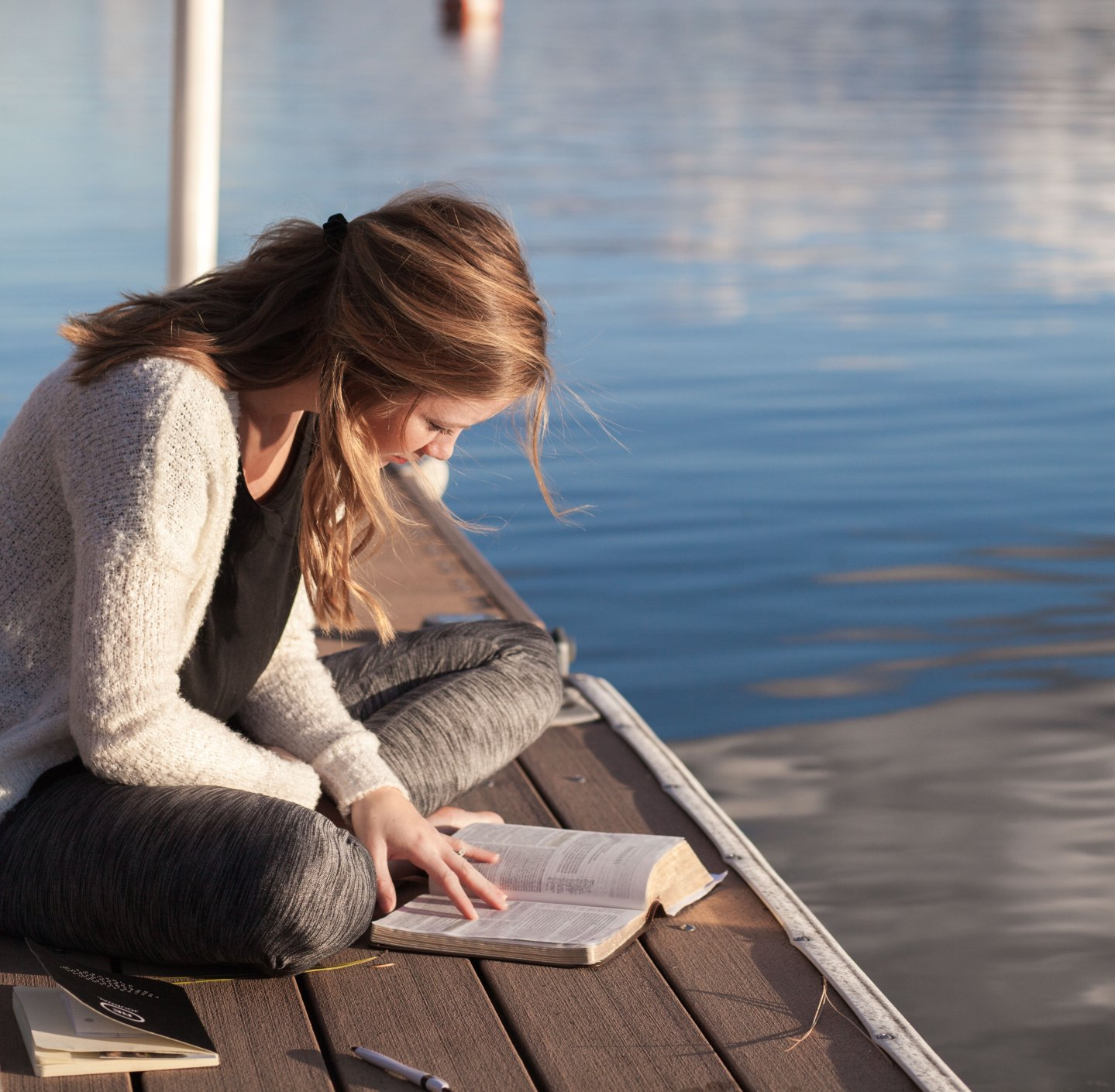 Woman reading her Bible on a dock