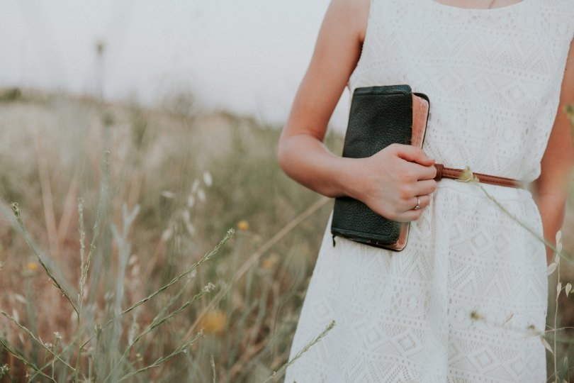Women in a field holding a Bible