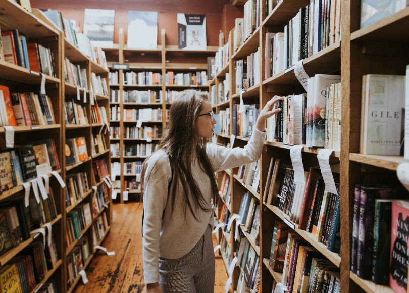 Woman looking through the shelves of the library