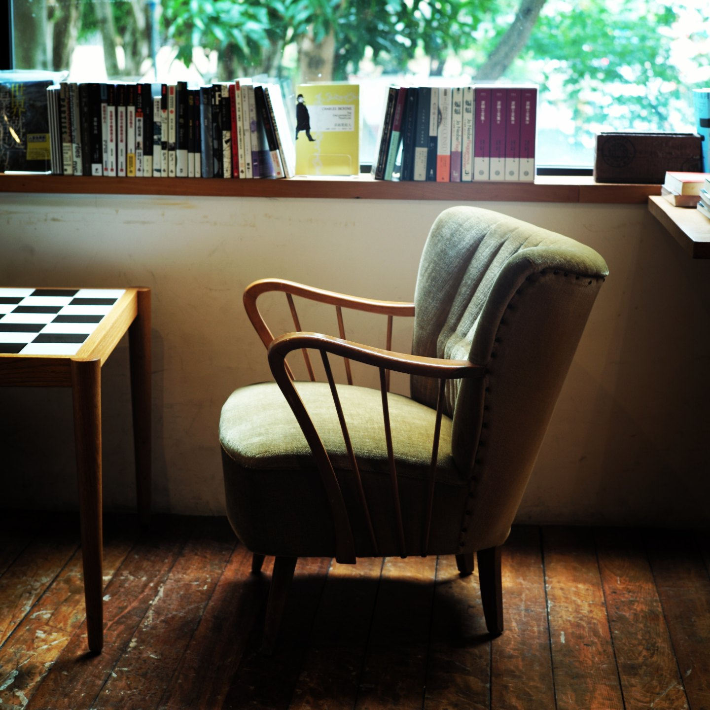 Chair, chessboard, and books lining a windowsill