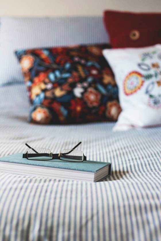 Book and glasses on a bed