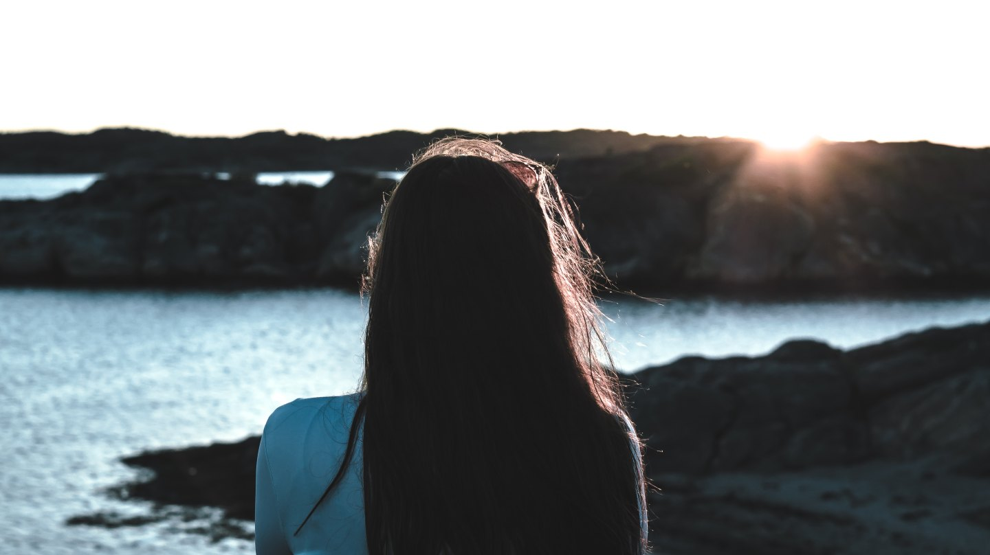 Woman looking out at the sea and the sun