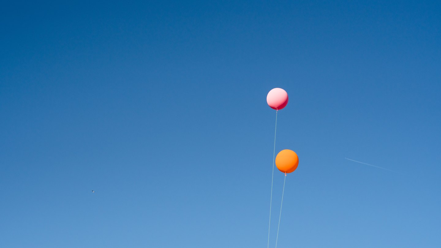 A pink and orange balloon floating in the sky