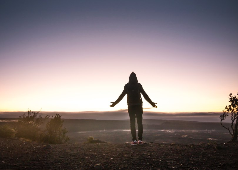 Person surrendering at sunset