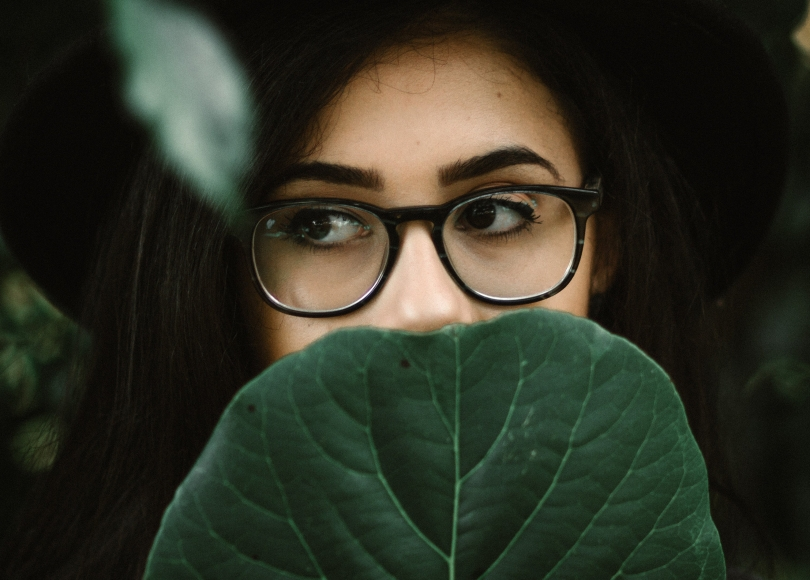 Woman covering her face with a leaf