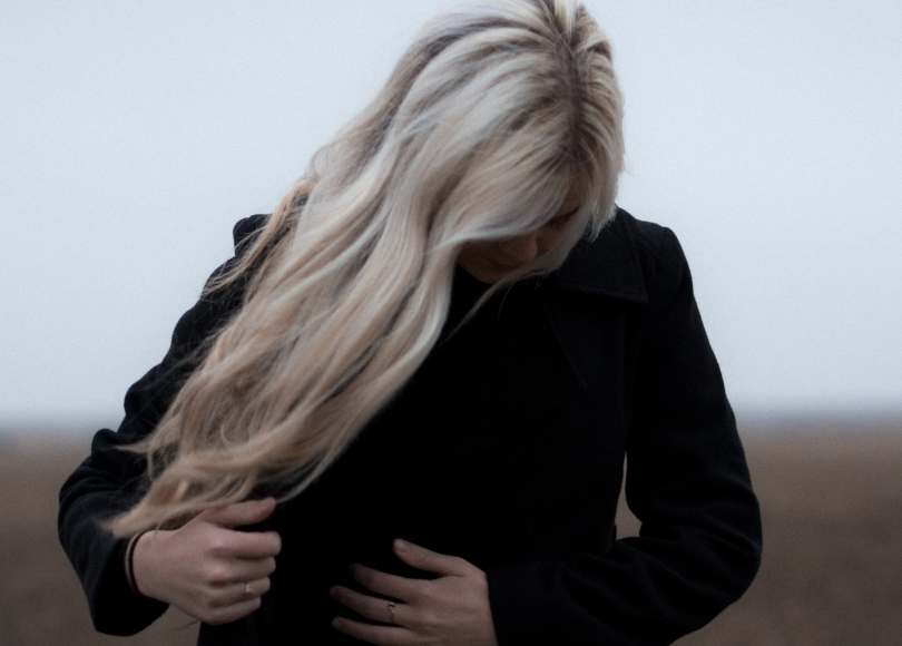 Woman with platinum hair fixing her jacket