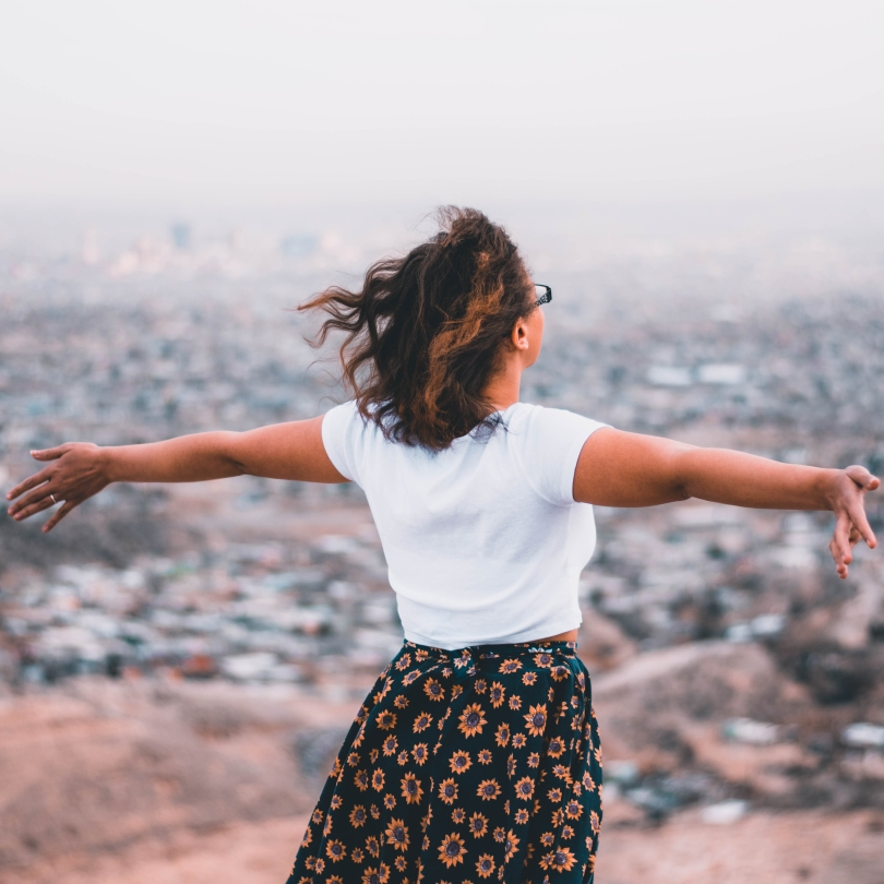 Woman with outstretched arms looking over the city