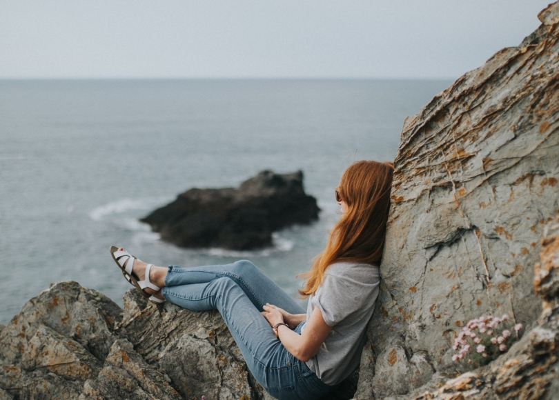 Woman sitting on a rock staring at the ocean