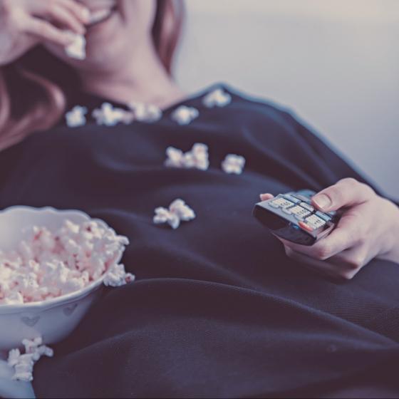 Woman bing-watching and eating popcorn