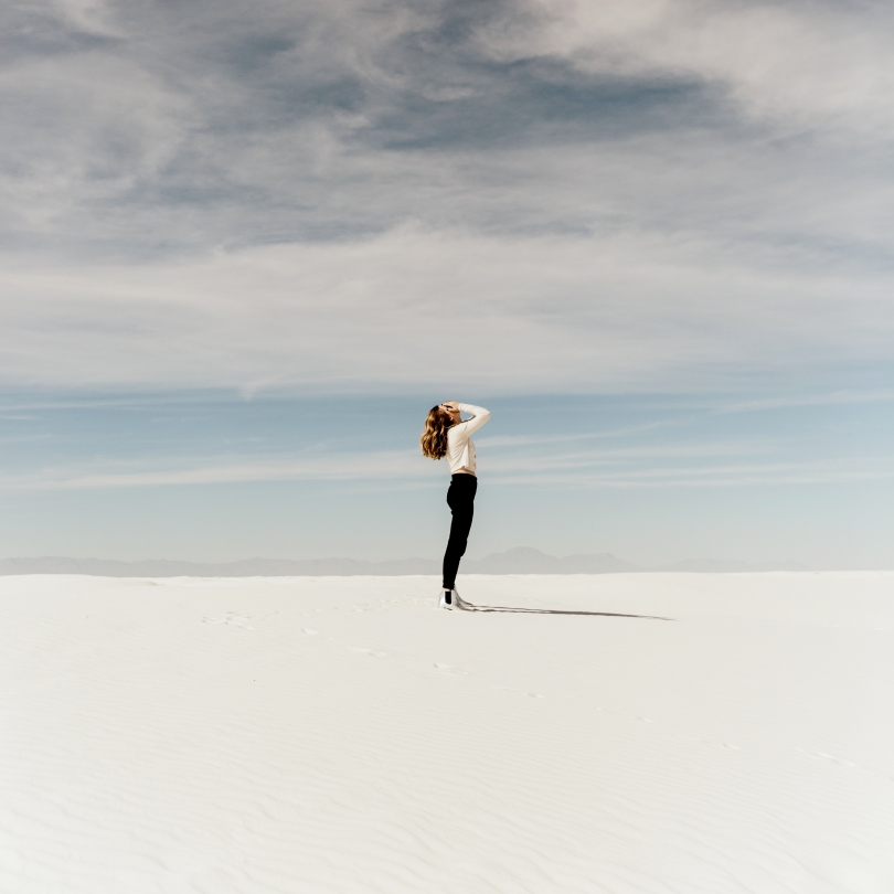 Woman covering her face as she looks up at the sky in the desert