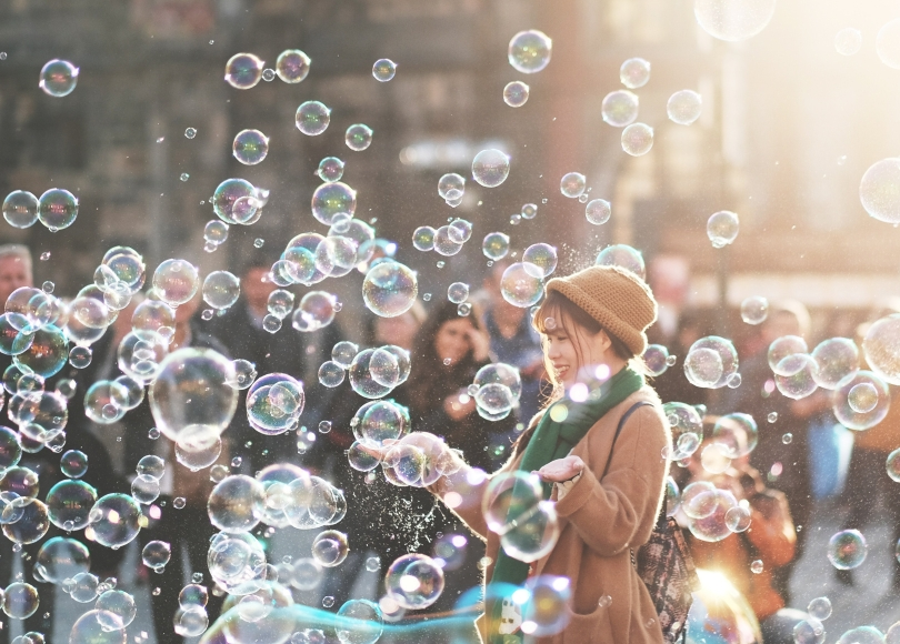 Woman in a crowd surrounded by bubbles