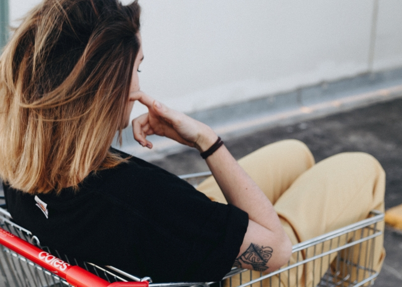 Woman contemplating in a shopping cart