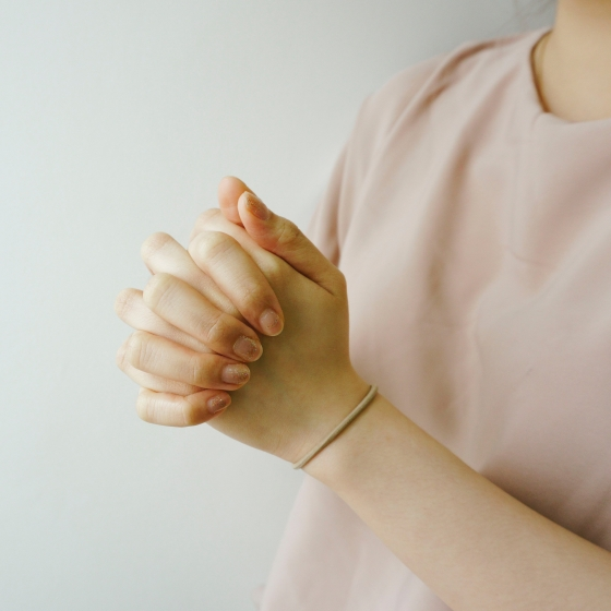 Woman's clasped hands praying