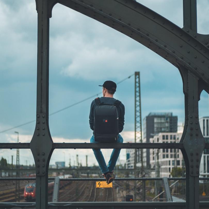 Man sitting looking out at a bridge