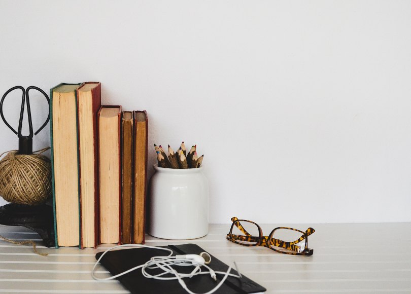 Desk with books, glasses, and headphones