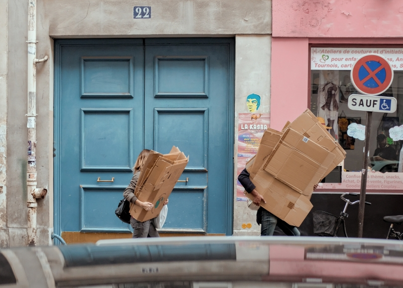 Two people walking with stacks of moving boxes