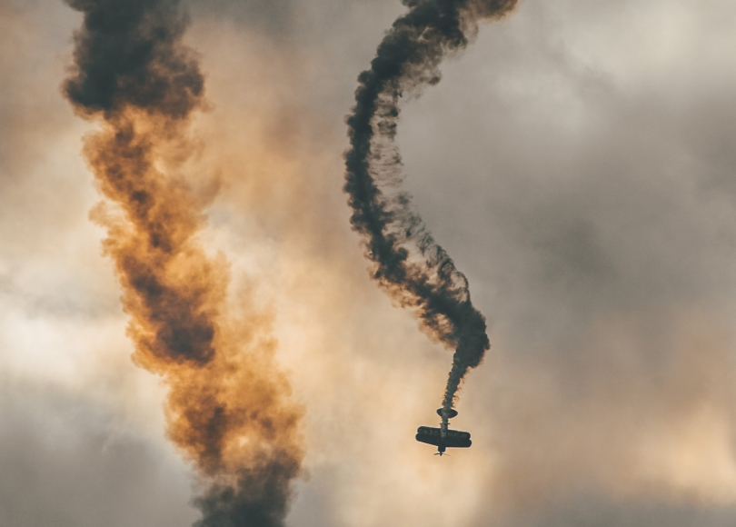 A plane descending with smoke trailing from it
