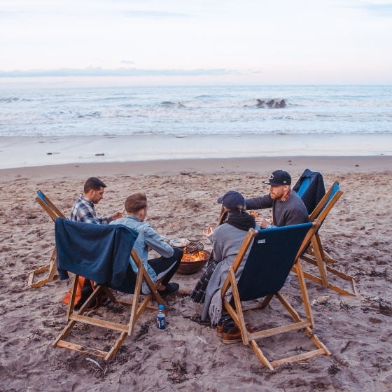 Group of friends chatting on the beach