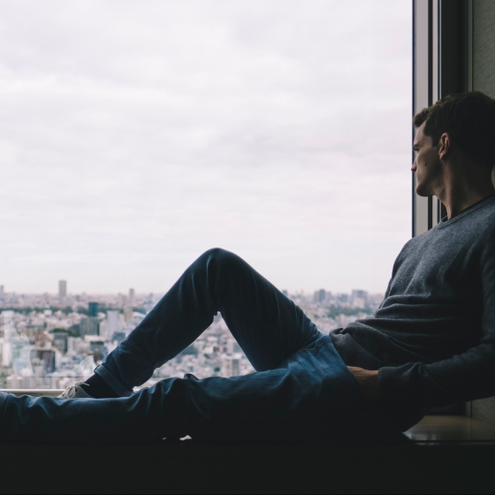 Man sitting on a window sill looking out the window
