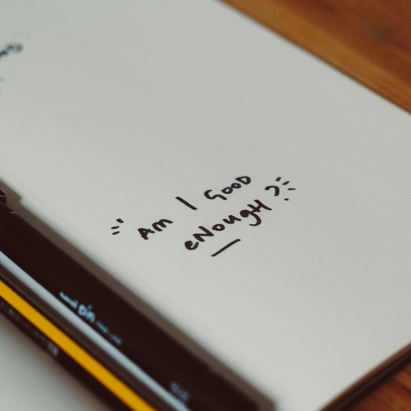 "Notebook with ""am I good enough?"" written on it"
