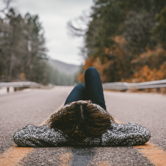 Woman lying in the middle of the road