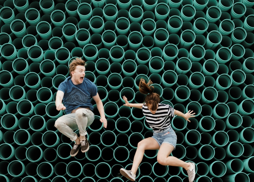 Two people jumping in front of a wall of green pipes