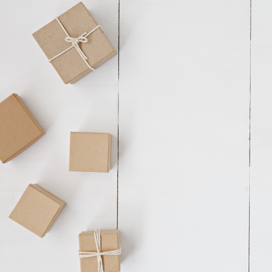 Gifts wrapped in brown kraft paper on a white background