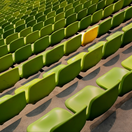 Green stadium seats with one yellow seat