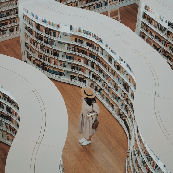 Woman looking through rows of books in a library