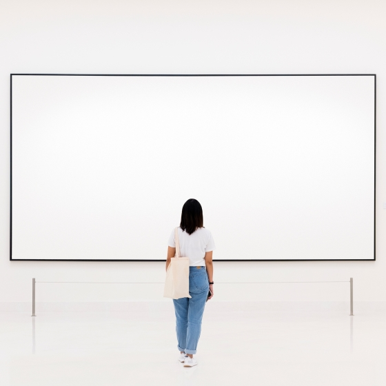 Woman looking at a white painting against a white wall